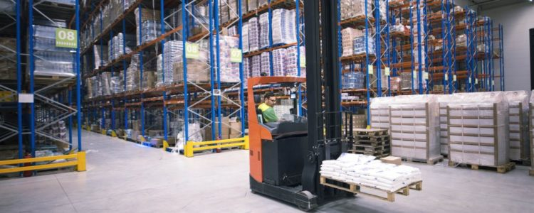 worker-operating-forklift-machine-and-relocating-goods-in-large-warehouse-center-min